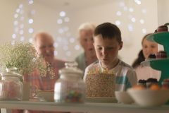 Multi-generation family celebrating birthday of grandson. At home with a birthday cake royalty free stock photo