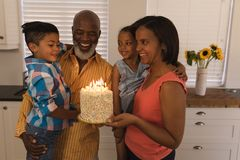 Multi-generation family celebrating birthday at home. Front view of a happy multi-generation African American family celebrating with birthday cake and birthday stock photos