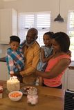 Multi-generation family celebrating birthday at home. Front view of a happy African American multi-generation family celebrating birthday with fire candles on royalty free stock photography