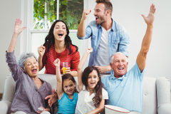 Multi generation family on cheering sofa. Multi generation family on sofa cheering while watching television at home Royalty Free Stock Photo