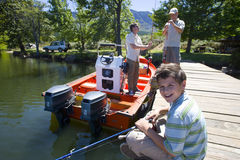 Multi-generation family on dock with fishing equipment and boat royalty free stock photography