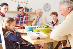 Multi Generation Family Eating Lunch At Kitchen Table royalty free stock images