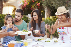 Multi Generation Family Eating Meal At Outdoors Together Royalty Free Stock Photos