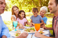Multi-generation family eating together outdoors Stock Photos