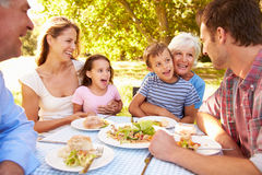 Multi-generation family eating together outdoors Royalty Free Stock Photo