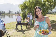 Multi-Generation Family Enjoying Barbeque By Lake Stock Photos