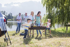 Multi-Generation Family Enjoying Barbeque By Lake Royalty Free Stock Photos