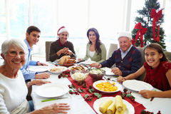 Multi Generation Family Enjoying Christmas Meal At. Home Smiling To Camera Stock Photography