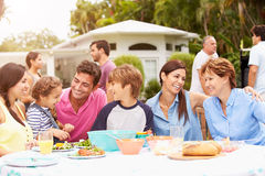 Multi Generation Family Enjoying Meal In Garden Together Royalty Free Stock Image