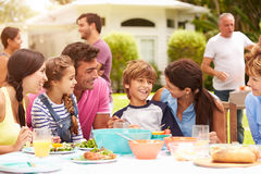 Multi Generation Family Enjoying Meal In Garden Together Stock Photos