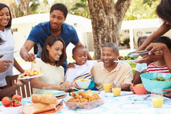 Multi Generation Family Enjoying Meal In Garden Together Stock Photo