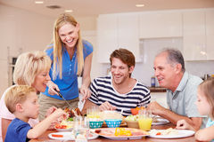 Multi Generation Family Enjoying Meal At Home Together Royalty Free Stock Photography