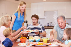 Multi Generation Family Enjoying Meal At Home Together Stock Photography