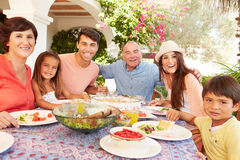 Multi Generation Family Enjoying Meal On Terrace Together Royalty Free Stock Photos