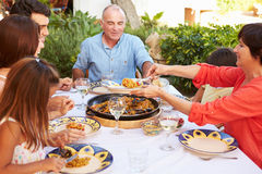 Multi Generation Family Enjoying Meal On Terrace Together Stock Image