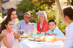 Multi-Generation Family Enjoying Outdoor Meal In Garden Stock Photography