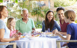 Multi Generation Family Enjoying Outdoor Meal Together Royalty Free Stock Image