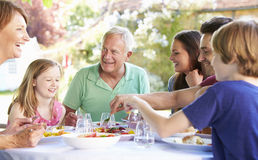 Multi Generation Family Enjoying Outdoor Meal Together Stock Photography