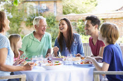 Multi Generation Family Enjoying Outdoor Meal Together Stock Photo