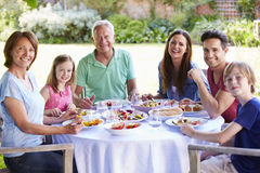 Multi Generation Family Enjoying Outdoor Meal Together Royalty Free Stock Photography