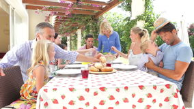 Multi Generation Family Enjoying Outdoor Meal Together