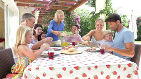 Multi Generation Family Enjoying Outdoor Meal Together stock footage