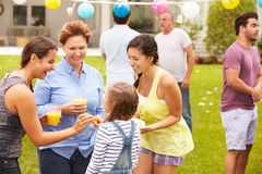 Multi Generation Family Enjoying Party In Garden Together Stock Images