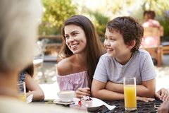 Multi Generation Family Enjoying Snack At Outdoor Caf� Together royalty free stock photography