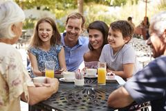 Multi Generation Family Enjoying Snack At Outdoor Caf� Together stock photos