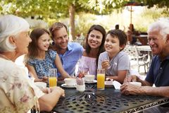 Multi Generation Family Enjoying Snack At Outdoor Caf� Together royalty free stock image