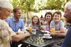 Multi Generation Family Enjoying Snack At Outdoor Caf� Together royalty free stock photo