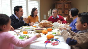 Multi Generation Family Enjoying Thanksgiving Meal. Camera tracks across table as extended family sit and enjoy thanksgiving dinner. Shot on Canon 5d Mk2 with a stock footage