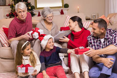 Multi generation family exchanging presents on couch Stock Photo