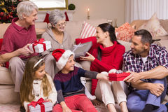 Multi generation family exchanging presents on sofa Royalty Free Stock Photo