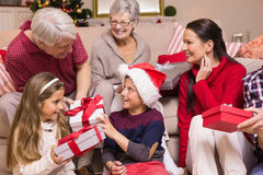 Multi generation family exchanging presents on sofa Stock Images