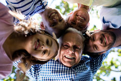 Multi generation family forming a huddle in park Royalty Free Stock Photos