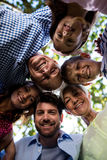 Multi generation family forming a huddle in park Royalty Free Stock Photography