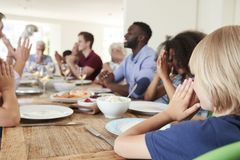 Multi-Generation Family And Friends Around Table Praying Before Meal At Party royalty free stock images