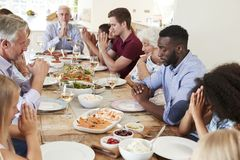 Multi-Generation Family And Friends Around Table Praying Before Meal At Party royalty free stock photos