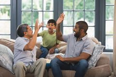 Multi-generation family giving high five while sitting together at home royalty free stock images