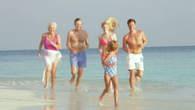 Multi Generation Family Having Fun In Sea On Beach Holiday Stock Photos