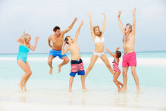 Multi Generation Family Having Fun In Sea On Beach Holiday. Smiling Stock Photography