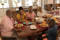 Multi-generation family having meal together on dining table at home stock photos