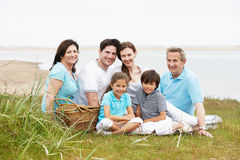 Multi Generation Family Having Picnic By Sea Stock Images