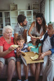 Multi-generation family having pizza in living room stock image