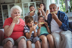 Multi-generation family having pizza together stock photography