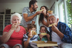 Multi-generation family having pizza together stock photos