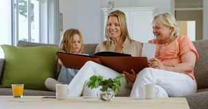 Multi-generation family looking at photo album in living room 4k. Multi-generation family looking at photo album in living room at home 4k stock footage