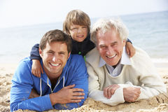Multi Generation Family Lying On Beach Together Stock Photo