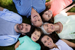 Multi generation family lying in park in a circle royalty free stock photo